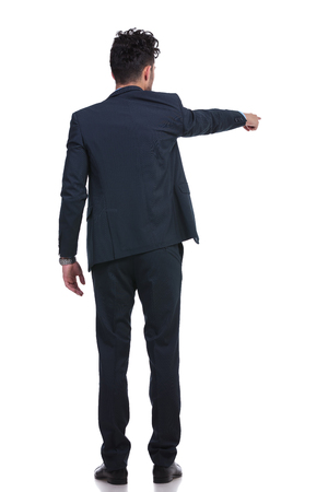 back picture of a young business man pointing his finger and choosing something  photo