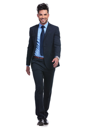 full body picture of a young smiling business man walking forward towards the camera photo