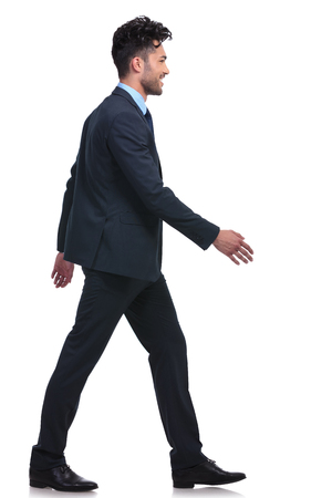side: side view of a young smiling business man walking forward