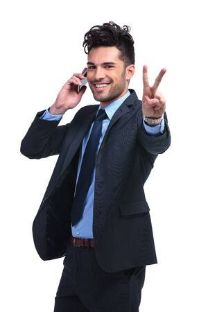 unshaved: young business man talking on the phone and making the victory hand gesture