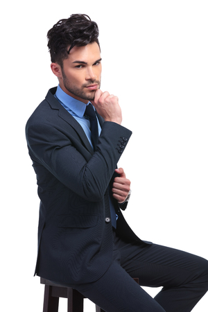 young seated fashion business man is wondering about something photo