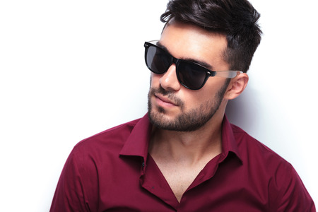 fashionable sunglasses: closeup portrait of a young casual man looking away from the camera. Stock Photo
