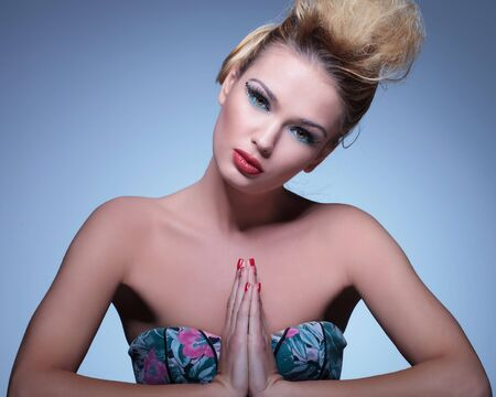 young beauty woman with nice makeup and red nails is praying photo