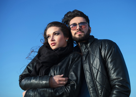 unshaved: young couple standing against blue sky thinking of future plans