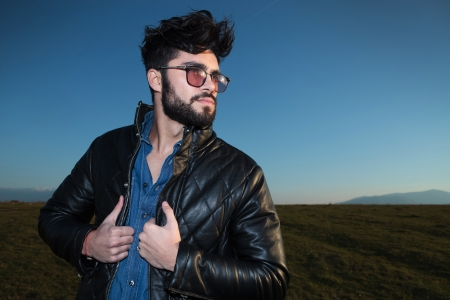 unshaved: side view of a fashion man holding his leather jacket and looking away from the camera against blue sky