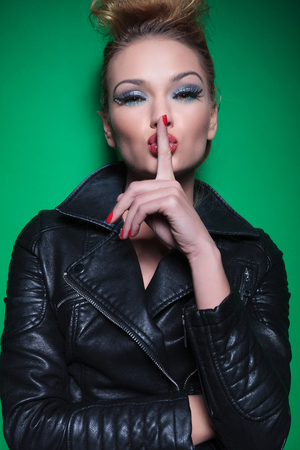 fashion woman with nice makeup and hairstyle is covering her mouth with her finger making the quiet gesture photo