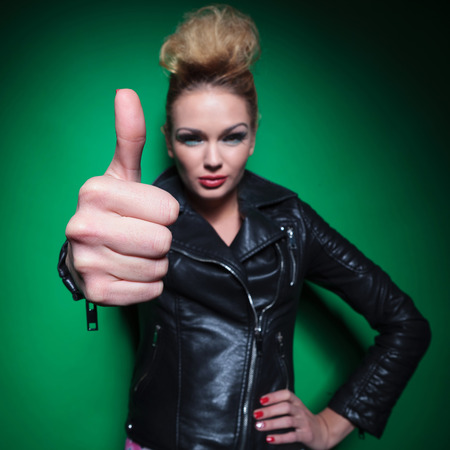 young positive fashion womanin leather jacket making the ok thumbs up sign photo