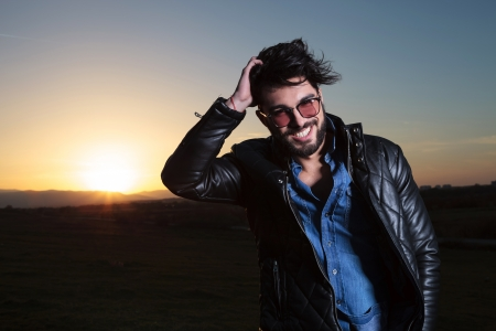leather jacket: smiling young man in leather jacket passing his hand through his hair in the dusk Stock Photo