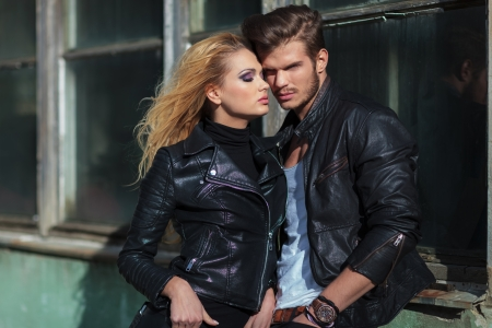 mode paar in lederen jassen die tegen een oud gebouw buiten