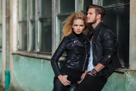 young fashion woman standing near her lover, outdoor picture near an old deserted building photo