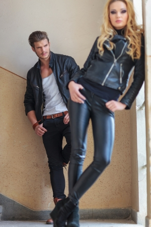young fashion man in leather clothes is checking a woman out from behind photo