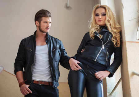 fashion man in leather jacket is pulling his girlfriend by her arm photo