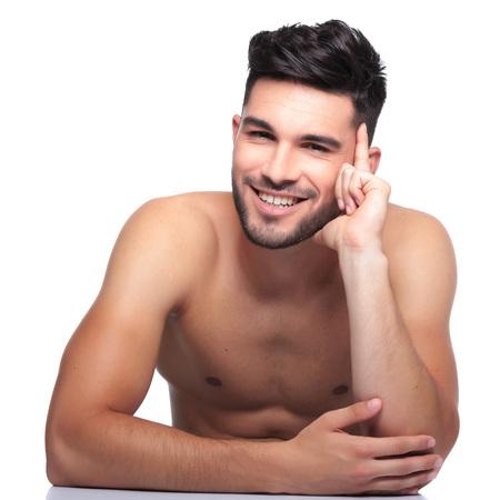 homme nu: souriant et beauté pensive homme nu est en riant sur un fond blanc Banque d'images