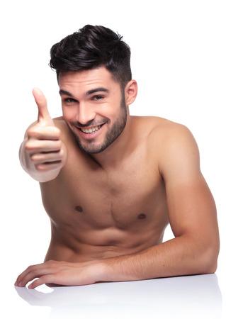 hombre desnudo: joven belleza desnuda haciendo las ok pulgares sube gesto de mano en el fondo blanco