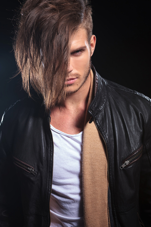 portrait of a fashion man with long hair looking at the camera on dark background photo