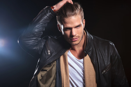 young fashion man passing his hand through his hair on dark background photo