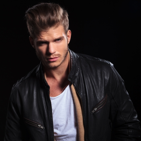 portrait of a young fashion man in leather jacket looking at the camera photo