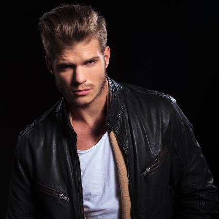 portret van een jonge mode man in leren jas kijken naar de camera