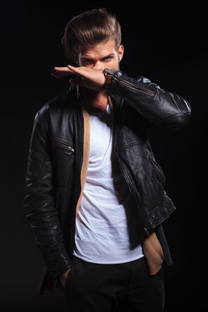 arrogant: arrogant fashion man in leather jacket is wiping his nose on dark background