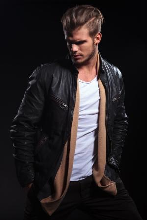 zijaanzicht van een mode-man in leren jas is op zoek naar zijn rug op een donkere achtergrond Stockfoto
