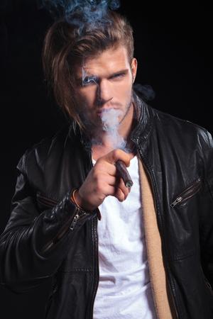 hombre fumando puro: retrato de un hombre joven con una chaqueta de cuero fumando un gran cigarro en un fondo negro