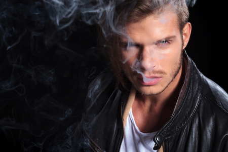 young fashion man in leather jacket covered in smoke on black background photo