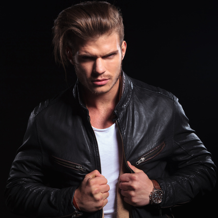 young fashion man expressing his anger and pulling his leather jacket on dark background photo