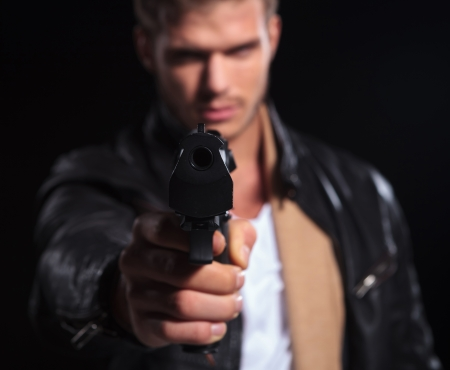 closeup picture of a young assasin pointing his gun to the camera on dark background