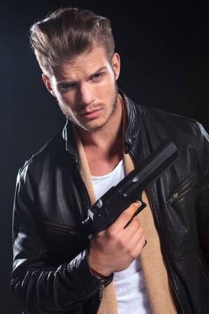 sicario: hitman joven en ropa de cuero que sostiene un arma grande en su fondo ondark mano