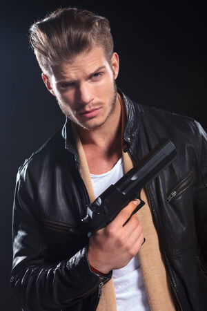 assasin: young hitman in leather clothes holding a big gun in his hand ondark background Stock Photo