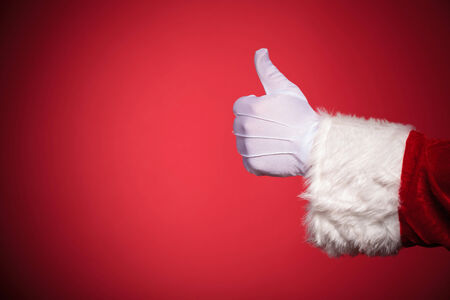 raise the thumb: Santa Claus hand showing thumbs up ok sign over red background with copy space