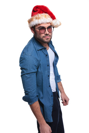 side view of an angry man in santa claus hat is looking at the camera photo