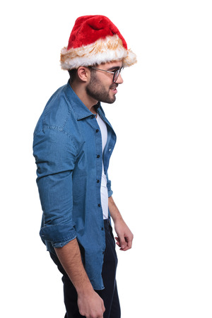 side view of a young man in santa hat is smiling and looking away from the camera on white background photo