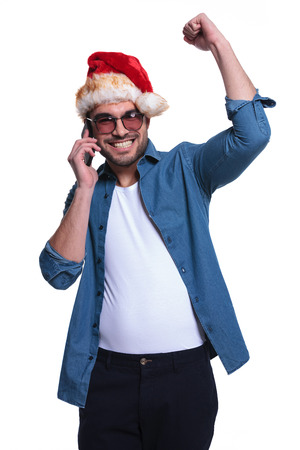 young man in santa claus hat is winning on the phone, on white background photo