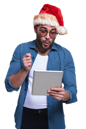 man in santa hat is reading something surprising on his tablet pad  photo