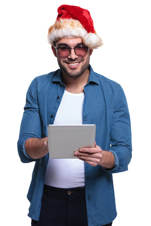 young man wearing santa hat is working on a tablet pad computer photo