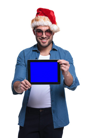 young man wearing santa hat is showing the blank screen of a tablet pad computer photo