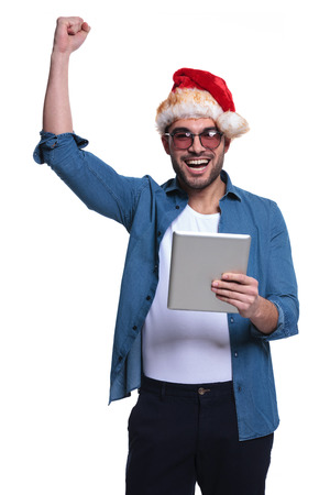 laughing man in santa man is winning while reading on his tablet pad on white background photo