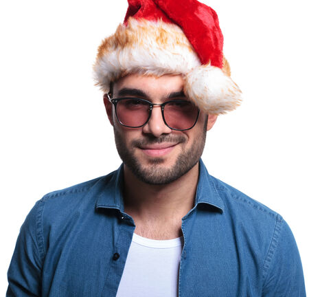 smiling face of a young man in casual clothes and santa claus hat , on white background photo