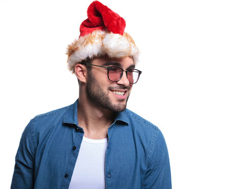 side view of a smilling young man wearing santa hat looking away from the camera photo