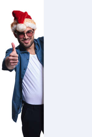 young santa man presenting a blank banner and making the ok thumbs up hand gesture  photo