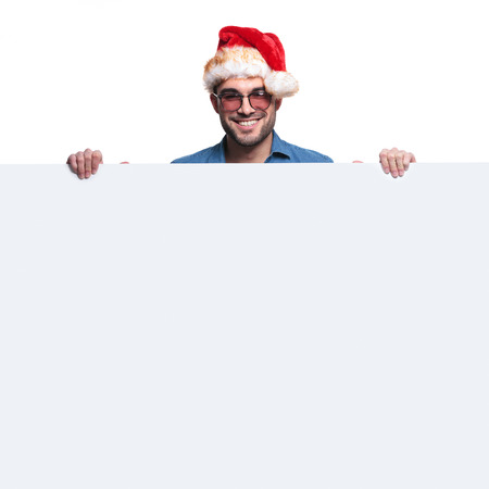 happy santa man is holding and presenting a big blank board on white background photo