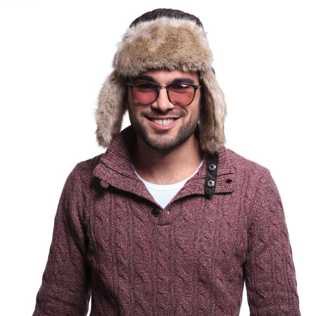 smiling casual man in winter clothes and furry hat, isolated on white background photo