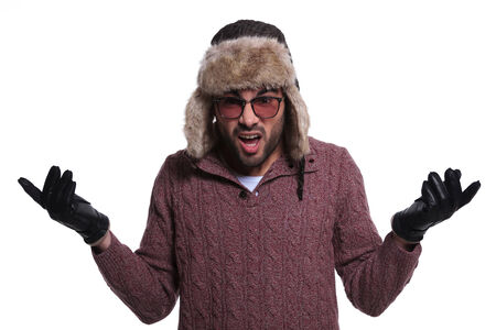 shocked young man in winter clothes and fur hat is having a bad reaction on white background