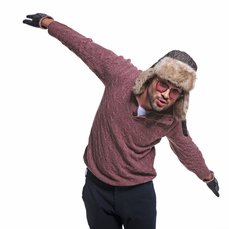 playful young man in winter clothes is impersonating an air plane  photo