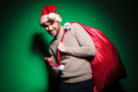 young santa man is playing with the bag on his shoulder on green background photo