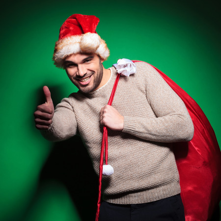 young santa man is making the ok thumbs up gesture on green background photo