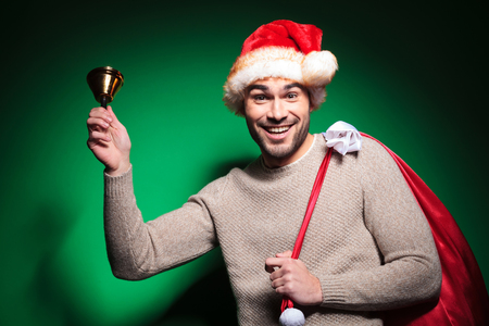 happy santa man ringing his little bell on green background photo