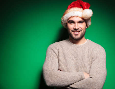 relaxed young man wearing santa claus hat standing with hands crossed on green background photo