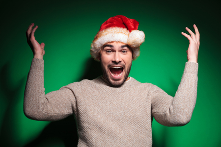 excited young santa man is winning and screaming of joy on green background photo